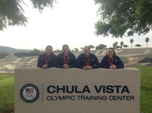 "Sam Leshnak '15 poses with three teammates behind the sign of the Olympic Training Center in Chula Vista, California. She was invited to the first ever Youth National Goalkeeper Training Camp in December 2012. Since then she has received several call ups and now trains on the U-20 WNT. Leshnak says, ""In the future, I see myself with a gold metal wrapped around my neck, with tears of joy."""
