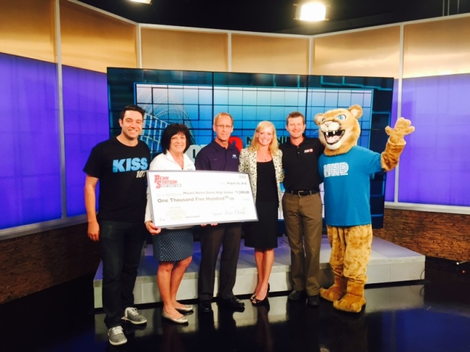 Athletic Director Mr. Mark Schenkel, Dean of Student Development Mrs. Judy Metcalf, and Retreat Director Ms. Maggie Prosser, in the cougar suit, went to Fox19 to receive the check from Penn Station East Coast Subs. It was presented to them by D Lo from Kiss107, Fox19 Sports Director Joe Danneman, and Deb Osterfeld from Penn Station.
