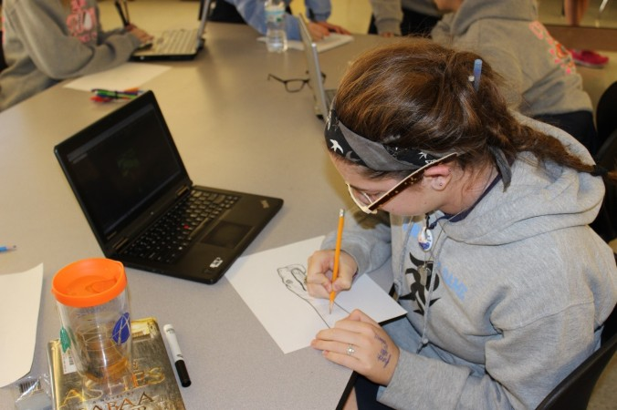 During Mrs. Beth Wurzelbacher's Art Foundations class, Julia Romano, junior, works on a rough sketch. This project calls for the students to turn a drawing into something that they will later paint onto their own hand. Romano decided to create a snake.
