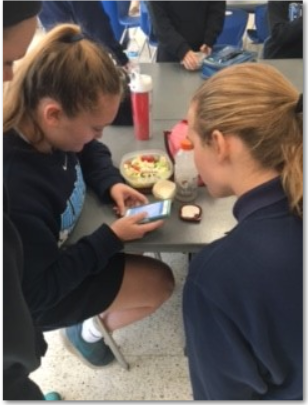 "Taking advantage of the new cell phone policy, juniors, Grace Hauck and Tori Beckelhimer use their phones during lunch to look up the latest high school volleyball standings. Beckelhimer and Hauck are both on the MND volleyball team and have been practicing hard for the end of the year tournament. ""We love this new cell phone policy especially during lunch,"" junior, Grace Hauck shares."