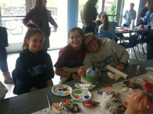 "Painting their winning pumpkin are seniors, Katie Schneider and Morgan Nagel, along with freshman, Peyton Fay. The group wrote the school year theme ""Do small things with great love"" on the background scene. Ms. Martis while judging said, ""It is very overwhelming and there are so many good ones."""