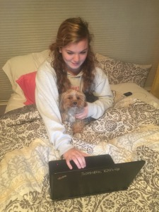 "Senior Olivia Combs enjoys the company of her beloved dog Marty while she studies.  Combs has had lots of practice figuring out what works and doesn't work when preparing for exams.  ""When studying, I always try to keep one of my dogs sitting in my lap. If I start to feel myself getting worked up over a math problem I can't solve or finding a mnemonic to memorize a series of things, I can just pet my dog and have him give me kisses for encouragement,"" she said."